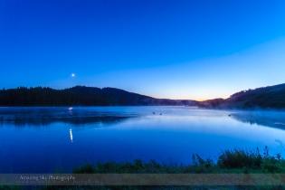 Moonset on a Misty Lake