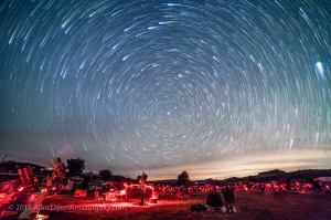 Circumpolar star trails over the upper field of the Texas Star Party, May 13, 2015. The star party attracts hundreds of avid stargazers to the Prude Ranch near Fort Davis, Texas each year to enjoy the dark skies. The three observing fields are filled with telescopes from the basic to sophisticated rigs for astrophotography. I aimed the camera to look north over the field to capture the stars circling around Polaris in circumpolar trails over about 1 hour. Some cloud and haze obscured parts of the sky. Lights from cities to the north add the sky glow at right. The streaks at top are from the stars of the Big Dipper. This is a stack of 55 exposures, each 1 minute long, at f/2.8 with the 14mm lens and Canon 5D MkII at ISO 3200. The foreground comes from a single image in the series, masked and layered in Photoshop. The images were stacked using the Long Trails tapering effect with the Advanced Stacker Actions from Star Circle Academy.