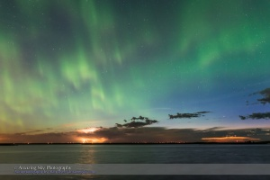 A sky-covering display of Northern Lights, here in the western sky over a distant thunderstorm on the Alberta prairies. I shot this June 22, 2015 on a night with a grand display over most of the sky, with the sky bright with solstice twilight. The site was on the south shore of Crawling Valley Lake in southern Alberta. This is one frame from a 350-frame time-lapse, taken with the Nikon D750 and 24mm lens,
