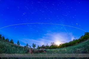 A pass of the International Space Station in the brightening twilight of dawn, on the morning of June 1, 2015, with the gibbous Moon setting to the southwest at right. The view is looking south, with the ISS travelling from right (west) to left (southeast) over several minutes. This was the last pass of a 4-pass night, May 31/June 1, starting at 3:55 am MDT this morning.  This is a composite stack of 144 exposures, each 2 seconds at f/2.8 with the 15mm full-frame fish-eye and ISO 3200 with the Canon 6D. The gaps are from the 1-second interval between exposures. The length of the trails and gaps reflects the changing apparent speed of the ISS as it approaches, passes closest, then flies away.  I stacked the exposures with the Advanced Stacker Actions from StarCIrcleAcademy.com, using the Lighten mode. The ground comes from a Mean blend of just 8 of the exposures to prevent shadows from blurring but to smooth noise.