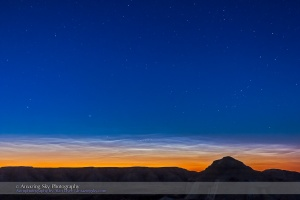 Noctilucent clouds (NLCs) over the silhouette of the badlands of Dinosaur Provincial Park in southern Alberta, on the night of June 15/16, 2015. The clouds remained low on the northern horizon and faded as the Sun angle dropped through the night but then reappeared in the northwest prior to dawn. The bright star at left is Capella, circumpolar at this latitude of 50° N.  This is a single exposure for 10 seconds at f/3.2 with the 16-35mm lens and at ISO 800 with the Canon 60Da.