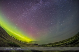 An aurora display to the northeast over the Milk River Valley and Writing-on-Stone Provincial Park in southern Alberta, night of July 22/23, 2015. The ground is lit by aurora light. The view is looking east to the rising autumn constellations of Cassiopeia and Perseus at left, and Andromeda and Pegasus at centre. The Milky Way runs from left to top centre. I shot this with the 15mm full-frame fisheye and Canon 6D. The sky is from one image, but the ground is from a stack of 4 images, mean combined, to smooth noise.