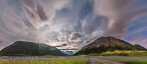 A panorama of the flower-filled Blakiston Valley on a moody moonlit cloudy night at Waterton Lakes National Park, June 24, 2015. The Big Dipper is at upper right, with its handle pointing to Arcturus at left of centre. Spica is at far left. A subtle halo surrounds the first quarter Moon which has just set behind Crandell Mountain at left.  This is a 9-segment panorama with the Nikon D750 and 24mm lens, mounted portrait, and stitched with Photoshop using spherical geometry and corrected with Wide Angle Adaptive Lens Correction to straighten the scene. Liberal use of Highlight and Shadow recovery in ACR and Shadows and Highlights in PS brought out the flower-filled foreground while retaining detail in the bright sky. Each segment was 30 seconds at f/2.8 and ISO 1600.