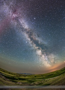 The summer Milky Way over the Milk River Valley and sandstone formations of Writing-on-Stone Provincial park, in southern Alberta. On the horizon are the volcanic Sweetgrass Hills in Montana. The red tint at top is from an aurora active that night and the ground is partly illuminated by green auroral light from the north. The Summer Triangle stars are at top left. Sagittarius is on the horizon sinking into the low clouds at botton right which are illuminated by lights from Sweetgrass, Montana. Clouds and smoke from forest fires to the west cut down the transparency and clarity of the sky this night, especially toward the horizon.  This is a stack of 4 x 3-minute tracked exposures for the sky, and 4 x 5-minute untracked exposures for the ground, all with the 15mm Canon full-frame fish-eye and Canon 6D at ISO 1000, on the iOptron Sky-Tracker unit.