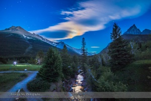 A nightscape photographer from one of my workshops, shooting in the moonlight at Red Rock Canyon, in Waterton Lakes National Park, Alberta. Clouds partly obscure the gibbous Moon but add a colourful iridescent corona around the Moon, which is reflected in the Red Rock Canyon Creek. This is an HDR stack of 5 exposures with the 14mm lens and Canon 6D, to preserve detail in the bright clouds and the disk of the Moon, and in the dark shadows.