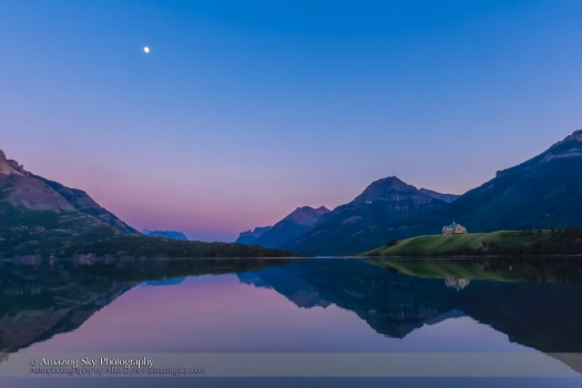 The waxing gibbous Moon over Upper Waterton Lake in Waterton Lakes National Park, Alberta with the iconic Prince of Wales Hotel in the distance, on a calm evening with still waters, rare in Waterton. This is an HDR stack of 3 exposures with the Canon 60Da and 16-35mm lens, shot from Driftwood Beach.