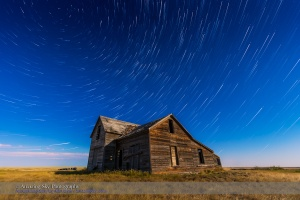 Circumpolar star trails circling above an old rustic and abandoned house near Bow Island, Alberta, with illumination from the nearly Full Moon. Cassiopeia is near centre. Polaris is at top left.  This is a stack of 140 frames from a time-lapse sequence with additional frames added for the first and last stars, and the ground coming from a mean combine stack of 8 frames to reduce noise. Each frame is 10 seconds at f/4 with the 16-35mm lens and ISO 1600 with the Canon 6D. Stacked with Advanced Stacker Actions, using the Ultrastreaks effect, from within Photoshop.