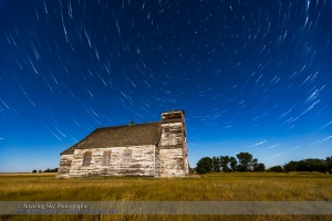 Circumpolar star trails over the historic but sadly neglected St. Anthony's Church between Bow Island and Etzikom, Alberta. The Big Dipper is at left, Polaris at top. The Roman Catholic church was built in 1911 by English, Russian German immigrants. It served a dwindling congregation until 1991 when it closed. At that time workers found a time capsule from 1915 with names of the priest and parisioners of the day. In summer of 2014 the Church suffered its latest indignity when the iron cross on its steeple tower was stolen. It was there when I stopped at this Church on a site scouting trip in May 2014. I planned to return on a moonlit night and did on July 29, 2015. A nearby house had been torn down and the cross was now gone.  This is a stack of 300 6-second exposures with the Canon 6D at ISO 1600 and 16-35mm lens at f/2.8. Bright light from a 13-day Moon lights the scene, making for very short exposures. The ground comes from one exposure to keep shadows sharp. The final stars also come from another single exppsure taken two minutes after the last trail image. I used the Advanced Stacker Actions to stack the trails.
