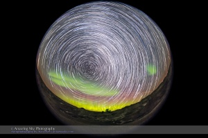 A composite stack of 198 images creating a circumpolar star trail image of the entire sky, with the motion of the stars and the Northern Lights over an hour recorded onto one frame.  The 8mm fish-eye lens take in almost all the sky, with the camera aimed northeast to the centre of the auroral arc, with Polaris, the centre of the sky's rotation, at left. The scene is at Dinosaur Provincial Park in Alberta, from September 11, 2015.  Each exposure was 20 seconds at f/3.5 with the Sigma 8mm lens and at ISO 6400 with the Canon 6D. The ground comes from a stack of 16 images taken early in the sequence turned into a smart object and mean combined with Mean stack mode, to average out and smooth noise. The sky comes from 198 exposures, Lighten stacked using the Advanced Stacker Actions from StarCircleAcademy.com.