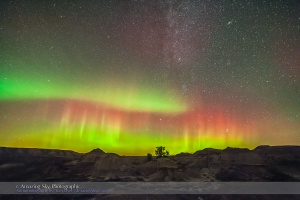 An aurora and the autymn Milky Way over the Badlands of Dinosaur Provincial Park, Alberta, on September 11, 2015. The stars, constellations and Milky Way of the autumn and early winter sky are rising in the northeast, including the objects: the Andromeda Galaxy at top, and the Pleiades at bottom.  This is one frame from a 200-frame time-lapse sequence, though in this image the ground comes from a Mean Combine stack of 7 images to smooth noise but the sky is from one image, each 30 seconds at f/2.8 with the Rokinon 14mm lens and Canon 5D MkII at ISO 3200 on a dark moonless night.