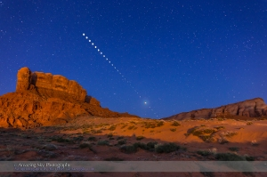 The total lunar eclipse of April 4, 2015 taken from near Tear Drop Arch, in western Monument Valley, Utah. I shot the totality images at 6:01 a.m. MDT, during mid-totality during the very short 4 minutes of totality. The mid-totality image is a composite of 2 exposures: 30 seconds at f/2.8 and ISO 1600 for the sky and landscape, with the sky brightening blue from dawn twilight, and 1.5 seconds at f/5.6 and ISO 400 for the disk of the Moon itself. Also, layered in are 26 short exposures for the partial phases, most being 1/125th sec at f/8 and ISO 400, with ones closer to totality being longer, of varying durations. All are with the 24mm lens and Canon 6D on a static tripod, with the camera not moved through the entire sequence. The short duration of totality at this eclipse lent itself to a sequence with one total phase image flanked by partial phases. The rocks are illuminated by lights from the community - light pollution but photogenic in this case - and partly from dawn glow in the east.