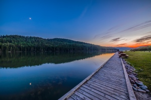The quarter Moon reflected in the waters of Reesor Lake, Alberta in Cypress Hills Interprovincial Park. Taken on July 5, 2014. This is with the 14mm Rokinon lens and Canon 6D at ISO800. This is a high dynamic range stack of6 exposures from 1/15 to 0.6 seconds taken just before using the camera to take a motion control time-lapse. The Moon was in conjunction with Mars (right of Moon) and Spica (left of Moon) but in the bright twilight they are not showing up here.