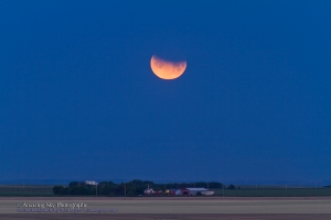 Partial eclipse of the Moon at moonset, morning of June 26, 2010, at about 5:00 am. Shot with 200mm telephoto and 1.4x teleconvertor, for 1/15th sec at f/5 and ISO 100, using Canon 7D.