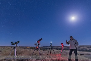 Me celebrating a successful total eclipse of the Moon during the final partial phases, observed and shot from Writing-on-Stone Provincial Park, Alberta, on September 27, 2015. I shot with 3 cameras, with a 4th to record the scene. Two of the cameras at centre are still shooting time-lapses of final partial phases. The camera at right was used to take long tracked exposures of the Milky Way during totality. The telescope at left was used just to look!