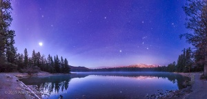 A panorama of roughly 120° showing a star- and planet-filled sky in the dawn twilight over Lake Annette in Jasper National Park, Alberta, on the morning of October 25, 2015.  At left, to the east, are the two bright planets, Venus (brightest) and Jupiter in a close conjunction 1° apart (and here almost merging into one glow), plus reddish Mars below them, all in Leo, with the bright star Regulus above them. Right of centre, to the south, is Orion and Canis Major, with the bright star Sirius low in the south. At upper right are the stars of Taurus, including Aldebaran and the Hyades star cluster. Venus was near greatest elongation on this morning.  No special filter was employed here — the hazy planets and stars and colourful star images comes naturally from a high haze over the sky this morning. It bloats the images of Venus and Jupiter so they almost merge.  The stars are partly reflected in the waters, with rising mist in the distance on the lake. Distant Whistler peak below Orion is lit by lights from the Jasper Townsite. The site is the shore of Lake Annette near the Jasper Park Lodge and site of the annual star party held as part of the Jasper Dark Sky Festival. I shot this scene the morning after the 2015 Festival. This is a panorama of 8 segments, shot with the 24mm lens mounted vertically (portrait), each for 25 seconds at f/2.8 with the Canon 6D at ISO 3200. Stitched with Photoshop, with some vertical scaling to reduce the distortion introduced by the pan mapping process.
