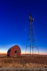 Mars, Venus and Jupiter (in that order from top to bottom) in a triangle, in conjunction, at an old farmstead near Vulcan, Alberta, in the morning twilight, October 28, 2015. Illumination is from the nearly Full Hunter's Moon in the west. The trio of planets were in Leo in a fine conjunction not to be repeated until November 21, 2111. Almost all of Leo is visible here, with Regulus, the constellation's brightest star, just to the right of the windmill blades at top. This is a stack of 6 exposures for the ground, mean combined to smooth noise, and one exposure for the sky, all  10 seconds at f/4 and ISO 800 with the Canon 6D and Canon 24mm lens.