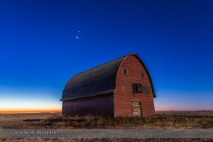 Mars, Venus and Jupiter (in that order from top to bottom) in a triangle, in conjunction, over an old red barn near Vulcan, Alberta, in the morning twilight, October 28, 2015. Illumination is from the nearly Full Hunter's Moon in the west. The trio of planets were in Leo in a fine conjunction not to be repeated until November 21, 2111.  This is a stack of 6 exposures for the ground, mean combined to smooth noise, and one exposure for the sky, all  10 seconds at f/4 and ISO 800 with the Canon 6D and Canon 24mm lens.