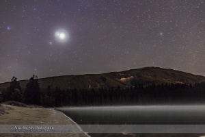Brilliant Venus, in conjunction with dimmer Jupiter above, and with even dimmer Mars below, at left here, on the morning of October 25, 2015 when Venus and Jupiter were only 1° apart.  I shot this from Lake Annette in Jasper National Park before the sky started to brighten with dawn twilight. High haze in the sky adds the glows around the stars and planets, in particular the colored halo around Venus. The mountain is the Watchtower. The site is used as the main star party location for the annual Jasper Dark Sky Festival. This is a 30-second exposure at f/2.8 with the 35mm lens and as ISO 1600 with the Canon 6D.