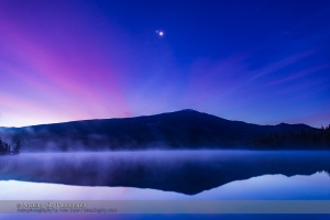 The conjunction of Venus (brightest), Jupiter (above Venus) and Mars (dimmer below Venus & Jupiter) looking east in the morning twilight on October 25, 2015, as seen from the west shore of Lake Annette, in Jasper National Park, Alberta. The mountain is the Watchtower. Morning mist covers the lake waters. Haze in the sky adds the natural glows around the planets — no filters were empolyed here. This is a layered stack of 4 images: 10, 5, 2.5 and 1.3-second exposures, with the longer exposure for the ground and the shorter exposures adding the sky to maintain tonal balance between the dark ground and bright sky. All with the 24mm lens and Canon 6D at ISO 400. It was not possible to capture the reflection of the planets in the water as they were too high in the sky.