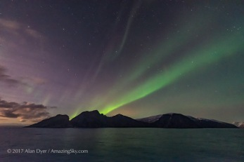 A dim but photogenic aurora on November 7, from the coast of Norway on the Hurtigruten ship the m/s Nordlys, in a view looking south to Pegasus and Andromeda, and over off-shore islands. The rising waning Moon off frame to the left illuminates the sky and landscape. This is a single 1-second exposure with the Sigma 14mm Art lens at f/1.8 and Nikon D750 at ISO 6400.