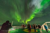 Aurora tourists watch and photograph the Northern Lights from the deck of the m/s Nordlys in October 2017 on the coast of Norway.