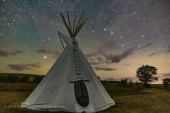 The Big Dipper and Arcturus (at left) over a single tipi at the Two Trees site at Grasslands National Park, Saskatchewan, August 6, 2018. This is a stack of 10 exposures, mean combined to smooth noise, for the ground, and one untracked exposure for the sky, all 30 seconds at f/2.8 with the 20mm Sigma lens and Nikon D750 at ISO 6400. Light cloud passing through added the natural star glows, enlarging the stars and making the pattern stand out. No soft focus filter was employed, and illumination is from starlight. No light painting was employed. Some airglow and aurora colour the sky. A Glow filter from ON1 Photo Raw applied to the sky to further soften the sky.