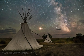 Mars and the Milky Way over the tipis at Two Trees area in Grasslands National Park, Saskatchewan on August 6, 2018. Some light cloud added the haze and glows to the planets and stars. Illumination is by starlight. No light painting was employed here. This is a stack of 8 exposures for the ground, mean combined to smooth noise, and a single untracked exposure for the sky, all 30 seconds at f/2.8 with the Sigma 20mm lens, and Nikon D750 at ISO 6400 with LENR on.