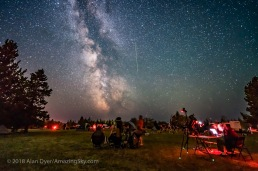 A Perseid meteor streaks down the Milky Way over the Saskatchewan Summer Star Party in the Cypress Hills of southwest Saskatchewan, at Cypress Hills Interprovincial Park, a Dark Sky Preserve. The Milky Way shines to the south. About 350 stargazers attend the SSSP every year. Observers enjoy their views of the sky at left while an astrophotographer attends to his camera control computer at right. This is a single exposure, 25 seconds, with the Laowa 15mm lens at f/2 and Sony a7III camera at ISO 3200.