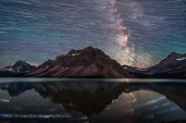 A blend of images to show the stars of the southern sky moving from east to west (left to right) over the Rocky Mountains at Bow Lake, in Banff, Alberta. The main peak at centre is Bow Peak. Crowfoot Glacier is at far left; Bow Glacier is at right below the Milky Way. A single static image shows the Milky Way and stars at the end of the motion sequence. The star trails and Milky Way reflect in the calm waters of Bow Lake this night on July 16, 2018, though they appear large and out of focus. This is a stack of 300 images for the star trails, stacked with the Ultrastreak function of Advanced Stacker Plus actions, plus a single exposure taken a minute or so after the last star trail image. The star trail stack is dropped back a lot in brightness, plus they are blurred slightly, so as to not overwhelm the fixed sky image. The sky images are blended with a stack of 8 images for the ground, mean combined to smooth noise in the ground. All are 30 seconds at f/2 with the 15mm Laowa lens and Sony a7III at ISO 3200. All were taken as part of a time-lapse sequence. Bands of airglow add the green streaks to the sky.