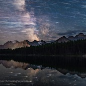 A blend of images to show the stars of the southern sky moving from east to west (left to right) over the peaks of the Continental Divide at Herbert Lake near Lake Louise, in Banff, Alberta. The main peak at left is Mount Temple. A single static image shows the Milky Way and stars at the end of the motion sequence. The star trails and Milky Way reflect in the calm waters of the small Lake Herbert this night on July 17, 2018. This is a stack of 100 images for the star trails, stacked with the Long Streak function of Advanced Stacker Plus actions, plus a single exposure taken a minute or so after the last star trail image. The star trail stack is dropped back a lot in brightness, plus they are blurred slightly, so as to not overwhelm the fixed sky image. The sky images are blended with a stack of 8 images for the ground, mean combined to smooth noise in the ground. All are 30 seconds at f/2.8 with the 24mm Sigma lens and Nikon D750 at ISO 3200. All were taken as part of a time-lapse sequence. Clouds moving in added the odd dark patches in the Milky Way that look like out of place dark nebulas. The reflected star trails are really there in the water and have not be copied, pasted and inverted from the sky image. They look irregular because of rippling in the water.