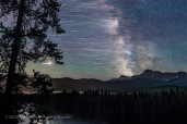 The stars trailing as they move east to west (left to right), ending with the Milky Way and Galactic Centre (right) over Storm Mountain and the Vermilion Pass area of the Continental Divide in Banff National Park, Alberta. Mars is the bright trail at left. Saturn is amid the Milky Way at right. This was July 15, 2018. The lights at left are from the Castle Mountain interchange at Highways 1 and 93. This is a stack of 8 exposures, mean combined to smooth noise, for the ground, plus 200 exposures for the star trails, and one exposure, untracked, for the fixed sky taken about a minute after the last star trail image. All 30 seconds at f/2.8 with the 24mm Sigma lens, and Nikon D750 at ISO 6400. The frames were taken as part of a time-lapse sequence. Dynamic Contrast filter from ON1 applied to the ground, and Soft and Airy filter from Luminar applied to the sky for a soft Orton effect.