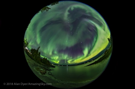An all-sky display of Northern Lights in the city of Yellowknife, from the end of the boardwalk at Rotary Park looking over the bay. This was on the night of Sept. 10/11, 2018 during a major solar storm, but in the subsiding hours after the sky cleared at about 2 am. The winter stars of Taurus and Gemini are rising. The Big Dipper is at far left. Cassiopeia is at the zenith. The view is looking east at centre. This is a mean stack of 8 exposures smoothed to reduce noise for the ground and one exposure for the sky, all 6 seconds at f/3.5 with the Sigma 8mm lens and Sony a7III at ISO 3200. The focus is soft.