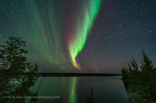 A faint green and red auroral curtain to the northwest over Tibbitt Lake on the Ingraham Trail near Yellowknife, NWT. The Big Dipper is right of centre; Arcturus setting on the horizon. This was September 8, 2018. This is a mean-combined stack of 8 exposures for the ground and water to smooth noise, and a single exposure for the sky, all 25 seconds at f/2 with the 15mm Laoawa lens and Sony A7III at ISO 1600.