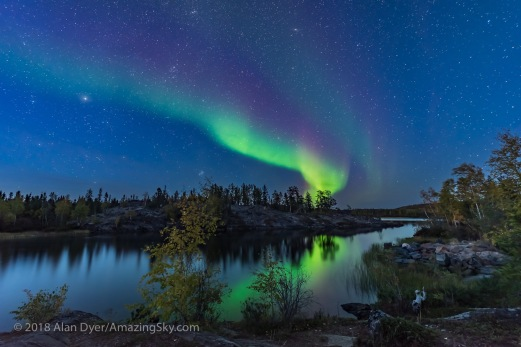 A display of Northern Lights starting up in the twilight, over the river leading out of Tibbitt Lake, at the end of the Ingraham Trail near Yellowknife NWT, on September 8, 2018. This was the start of a fabulous display this night. Capella and Auriga are at left; the Pleiades is rising left of centre; the Andromeda Galaxy is at top. This is a mean-combined stack of 7 exposures for the ground to smooth noise and one exposure for the sky and partially for the reflection, all 25 seconds at f/2.5 with the 14mm Sigma Art lens and Nikon D750 at ISO 1600.