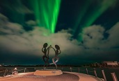 "The Northern Lights over the ""United in Celebration"" sculpture at the Somba K'e Civic Plaza on Frame Lake in downtown Yellowknife, NWT, on September 14, 2018. The Prince of Wales Museum is at far right. This is a stack of 5 images for the ground to smooth noise and one image for the sky, all 6 seconds at f/2 with the 15mm Laoawa lens and Sony a7III at ISO 400."