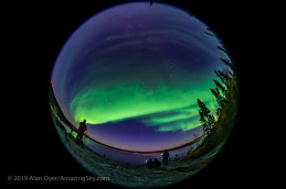 A 360° fish-eye view of the Northern Lights over Prelude Lake near Yellowknife, NWT, Canada, on September 9, 2019, with photographers in the foreground shooting the Lights from the viewpoint above the lake. Polaris is near the centre; the Big Dipper and Ursa Major are at lower left; Cassiopeia is at upper right. Andromeda and Pegasus are rising at far right. Arcturus is setting at far left. This is a single shot with the 8mm Sigma lens at f/3.5 on the Sony a7III for 10 seconds at ISO 3200. Moonlight also provides some of the illumination. Accent AI filter applied to the ground with Topaz Studio 2.0