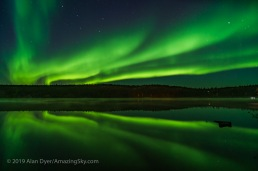"""Reflections of the Northern Lights in the calm waters of Madeline Lake on the Ingraham Trail near Yellowknife, NWT on Sept 7, 2019. This is one of a series of """"reflection"""" images. The Big Dipper is at left; Capella at far right. This is a single 8-second exposure with the 15mm Laowa lens at f/2 and Sony a7III at ISO 1600."""