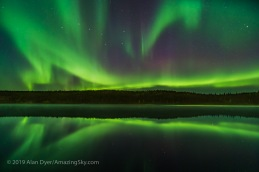 "Reflections of the Northern Lights in the calm and misty waters of Madeline Lake on the Ingraham Trail near Yellowknife, NWT on Sept 7, 2019. This is one of a series of ""reflection"" images. The Big Dipper is at left. Capella is at right. This is a single 13-second exposure with the 15mm Laowa lens at f/2 and Sony a7III at ISO 1600."
